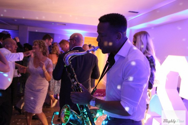 Saxophonist performs to dancing Wedding guests by large light up letters