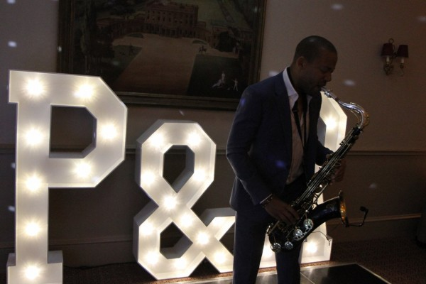Saxophonist plays during Wedding in front of large light up letters