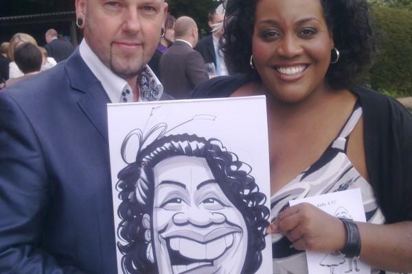 Alison Hammond and George G Williams hold a caricature of her drawn at a Wedding